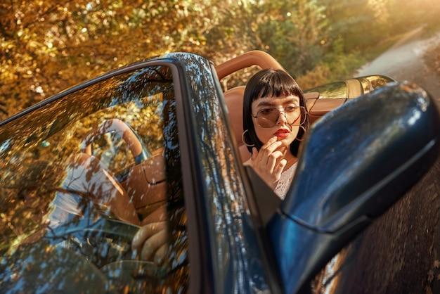 Привлекательная молодая женщина применяет макияж, глядя в зеркало на отражение