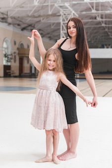 Attractive young woman assisting ballerina girl in dance class