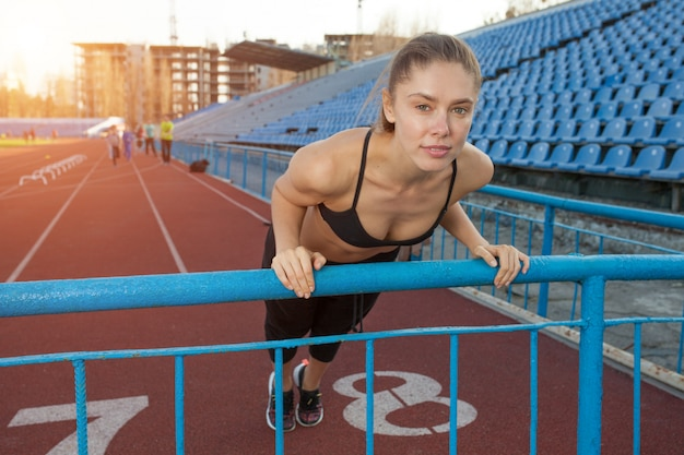 Attractive young woman athlete doing plank exercise on stadium