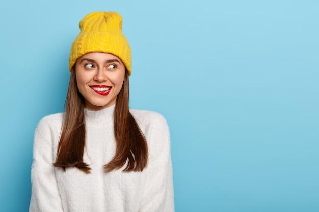 매력적인 젊은 여성이 붉은 입술을 물고, 무언가에 대해 생각하고, 멀리 보이며, 곧은 검은 머리카락을 가지고 있으며, 노란 모자를 쓰고 따뜻한 흰색 스웨터를 입습니다.