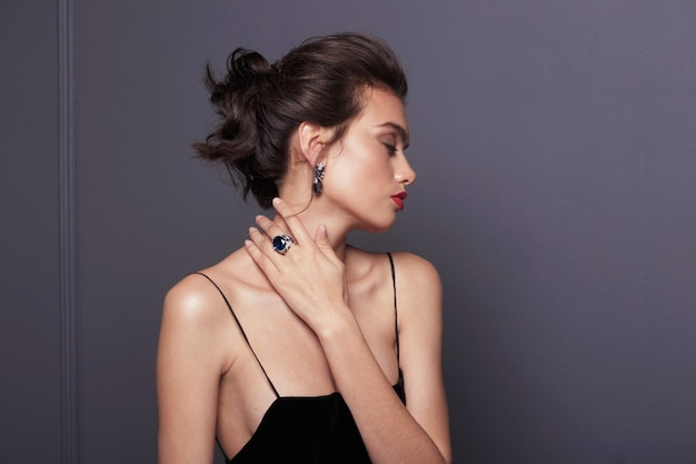 Attractive young woman in black dress with bare shoulders, wears blue stone earrings and rings over grey dark background.