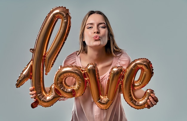 Attractive young woman in blouse is standing with air balloon labeled love in hands blows a kiss on grey.