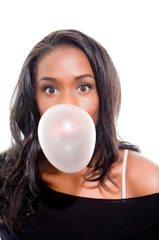 Attractive young woman blowing bubble gum with surprised expression