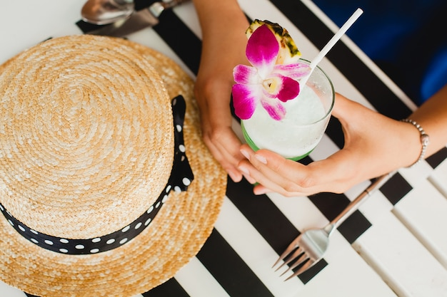 Attractive young woman in blue dress and straw hat wearing pink sunglasses, drinking alcohol cocktail on tropical vacation and sitting at table in bar