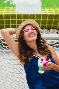 Attraente giovane donna in abito blu e cappello di paglia indossando occhiali da sole rosa bevendo cocktail alcolici in vacanza seduto in amaca in abito stile estivo, sorridendo felice in atmosfera di festa