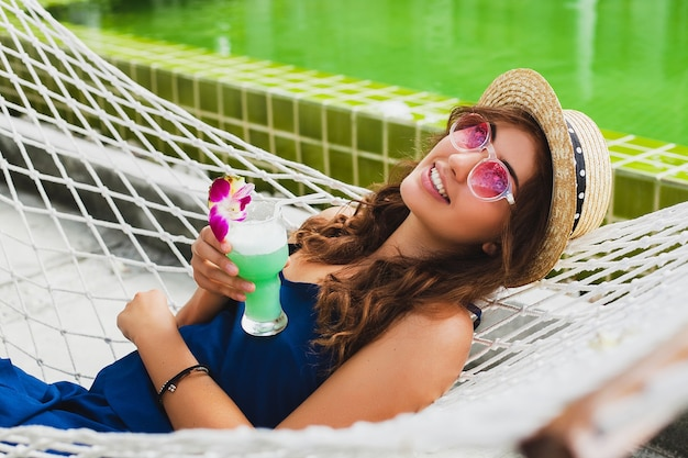 Attractive young woman in blue dress and straw hat wearing pink sunglasses drinking alcohol cocktail on vacation sitting in hammock in summer style outfit, smiling happy in party mood