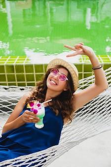 Attraente giovane donna in abito blu e cappello di paglia che indossa occhiali da sole rosa, bere cocktail alcolici in vacanza e seduto in amaca