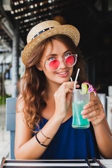 Attraente giovane donna in abito blu e cappello di paglia che indossa occhiali da sole rosa bevendo cocktail alcolici in vacanza tropicale seduto al tavolo in un bar in abito stile estivo, sorridendo felice in atmosfera di festa