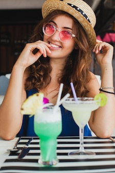 Attractive young woman in blue dress and straw hat wearing pink sunglasses, drinking alcohol cocktails on tropical vacation and sitting at table in bar