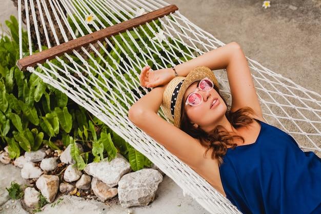 Attraente giovane donna in abito blu e cappello di paglia che indossa occhiali da sole rosa rilassante in vacanza sdraiato in amaca in abito stile estivo, sorridendo felice
