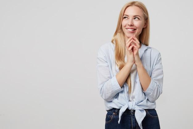 Attraente giovane donna in maglietta blu e jeans sorridendo maliziosamente e guardando lontano, strizzare gli occhi e mordere underlip con i palmi piegati, isolato