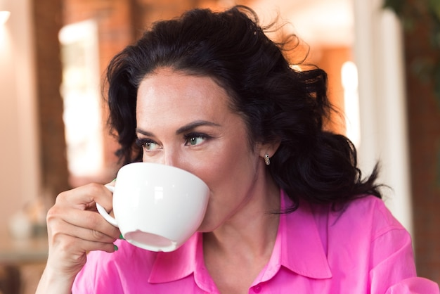 Attractive young woman brunette drinking coffee in modern cafe