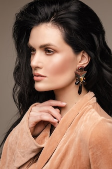 오래 건강 한 머리카락, 완벽 한 피부와 세련 된 귀걸이와 매력적인 젊은 여자 갈색 머리, 초상화를 닫습니다.