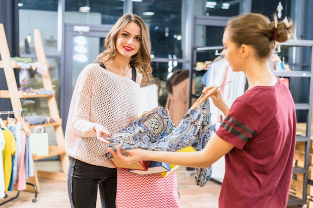 Attractive young woman buying clothes in apparel store