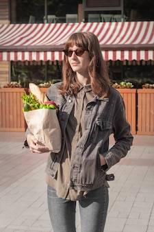 Attractive young woman in casual style clothes holding groceries bought from local vegetable and grocery store or market.