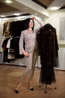 가게에서 옷걸이에서 모피 코트를 선택하는 매력적인 젊은 여자