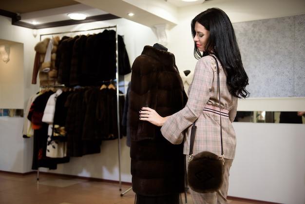 店のハンガーから毛皮のコートを選ぶ魅力的な若い女性