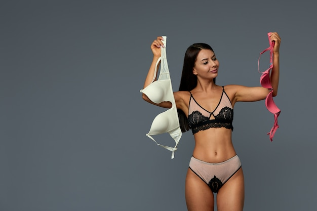 Attractive young woman choosing which bra to wear, white or red