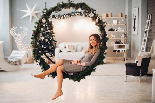 Attractive young woman on christmas swings. christmas tree.