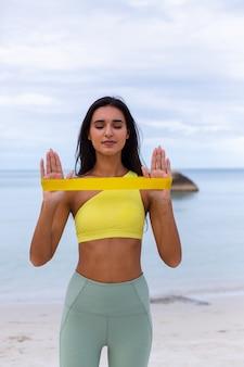 Attraente giovane donna in abbigliamento sportivo colorato sulla spiaggia