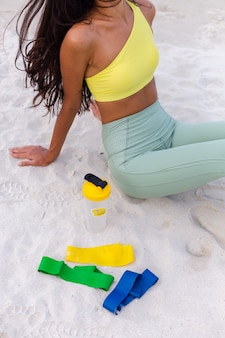 Attractive young woman in colorful sport wear on beach