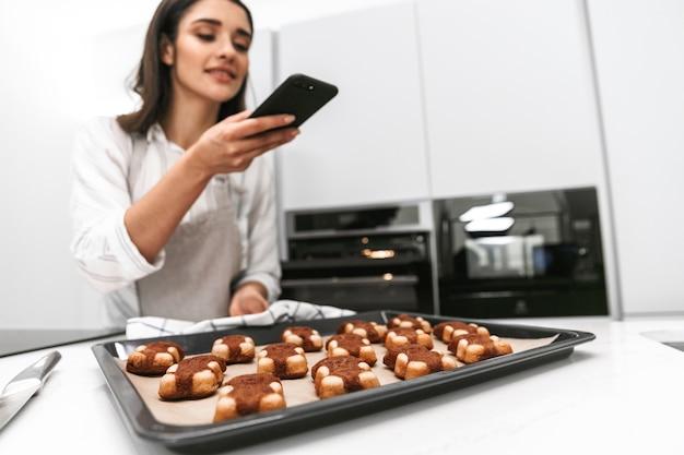 Привлекательная молодая женщина готовит вкусное печенье на подносе, стоя на кухне и фотографируя