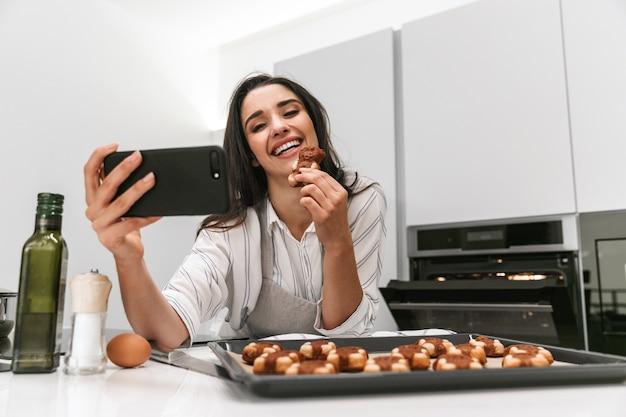Привлекательная молодая женщина готовит вкусное печенье на подносе, стоя на кухне, принимая селфи