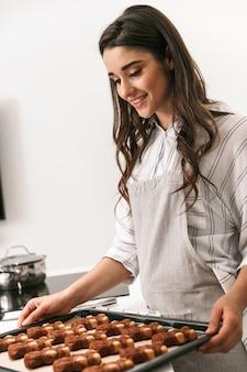 キッチンに立っている間トレイでおいしいクッキーを調理する魅力的な若い女性