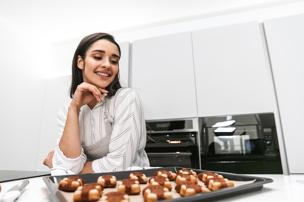 Привлекательная молодая женщина готовит вкусное печенье на подносе, стоя на кухне