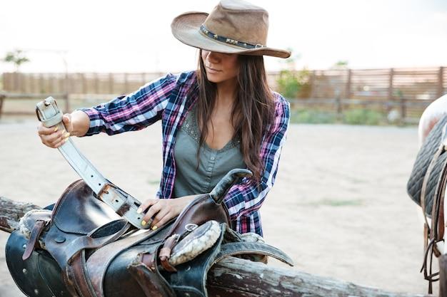 모자를 쓰고 말을 타기 위한 안장을 준비하는 매력적인 젊은 여성 카우걸