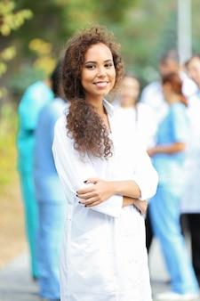 Привлекательная молодая женщина-врач с буфером обмена в руках против группы медиков, на открытом воздухе