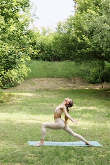An attractive young woman does yoga in the park in the summer yoga instructor