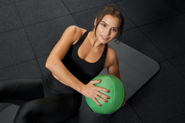 マットの上でカーディオン運動をしている魅力的な若い女性