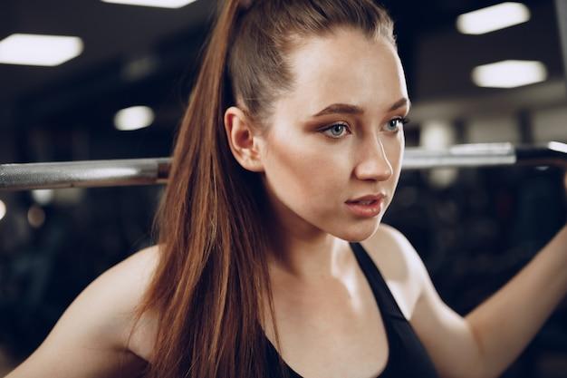魅力的な若い女性は腕の筋肉のエクササイズとジムに戻る