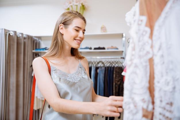 쇼핑을하고 옷가게에서 옷을 선택하는 매력적인 젊은 여자