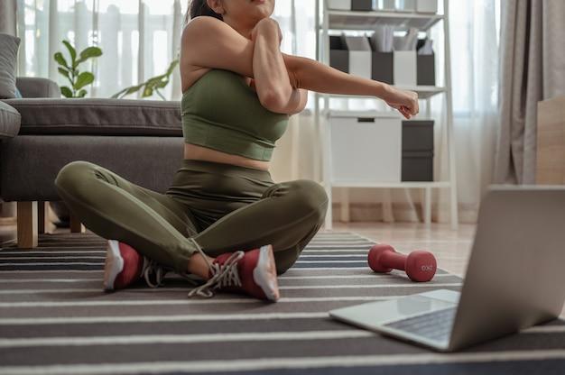 自宅でオンラインでヨガストレッチヨガをしている魅力的な若い女性検疫中に屋内で運動する