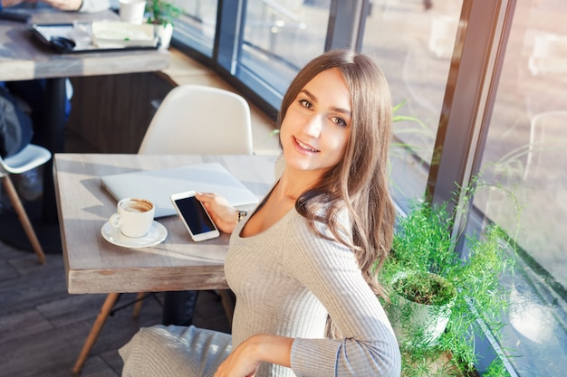 Attractive young woman in dress in cafe uses mobile phone and laptop