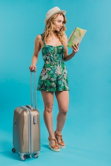 Attractive young woman in dress and hat holding map and suitcase