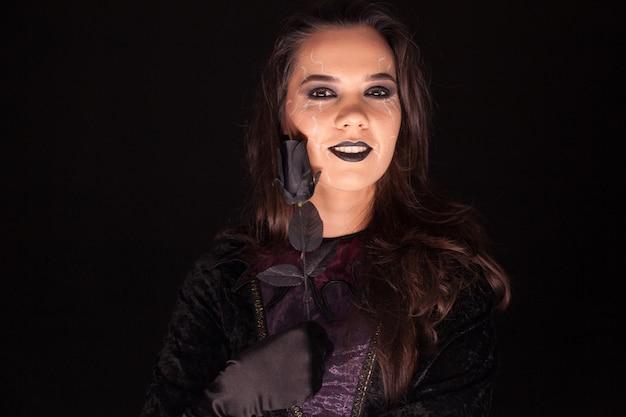 매력적인 젊은 여성이 할로윈을 위해 검은 배경 위에 장미를 들고 고딕 마녀처럼 차려입었습니다.