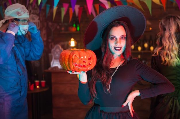 カメラの前でポーズをとるハロウィーンの魔女のような格好をした魅力的な若い女性。バックグラウンドで不気味な医者。