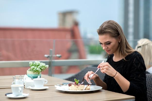 Привлекательная молодая женщина пьет кофе и ест торт на открытой террасе на крыше ресторана Premium Фотографии