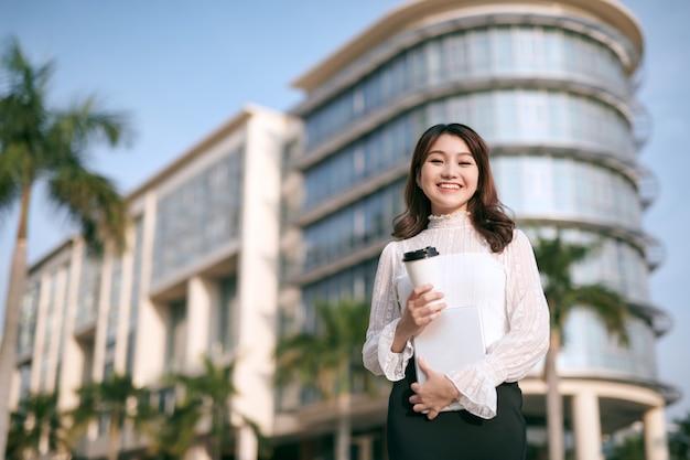 Привлекательная молодая женщина пьет кофе и читает свой сенсорный планшет, стоя возле коммерческого здания
