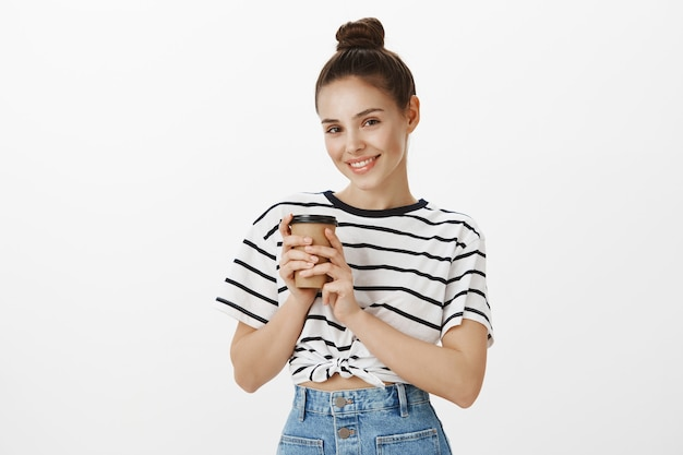 Attractive young woman drinking coffee, order drink from cafe takeaway