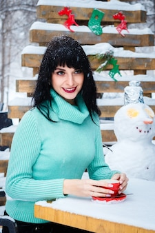 魅力的な若い女性は雪の降る冬の日にストリートカフェでコーヒーを飲みます