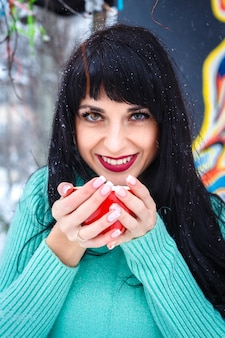 魅力的な若い女性が雪の降る冬の日にストリートカフェでコーヒーを飲むカメラを見て笑顔