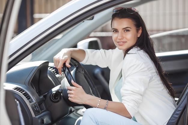차를 운전하는 매력적인 젊은 여자. 자동차에서 멋진 여자입니다. 차에 부유 한 성인 여성. 자신감이 여자.