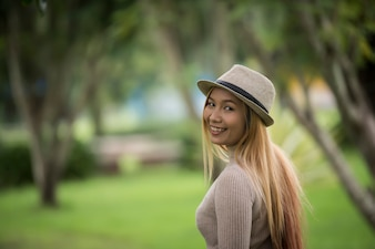 Attractive young woman enjoying her time outside in park with nature park background.