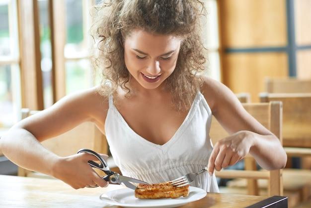Привлекательная молодая женщина наслаждается обедом в ресторане, весело улыбаясь во время резки стейка на гриле ножницами.