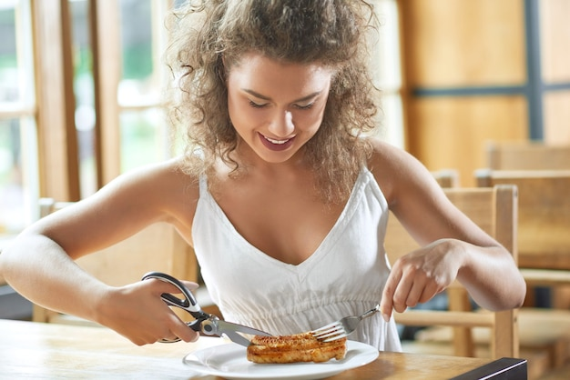 Attractive young woman enjoying lunch at the restaurant smiling cheerfully while cutting grilled steak with scissors.