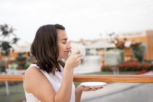 Attraente giovane donna godendo la mattina all'aperto con una tazza di caffè e un piattino in mano.